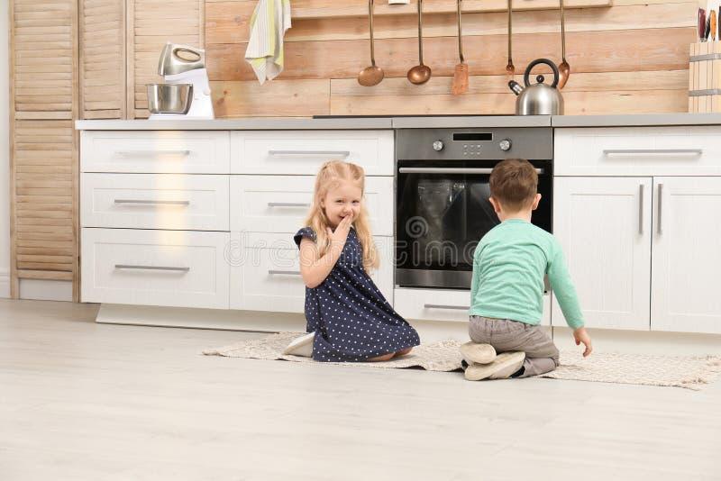 Śliczni dzieci siedzi blisko piekarnika zdjęcia stock