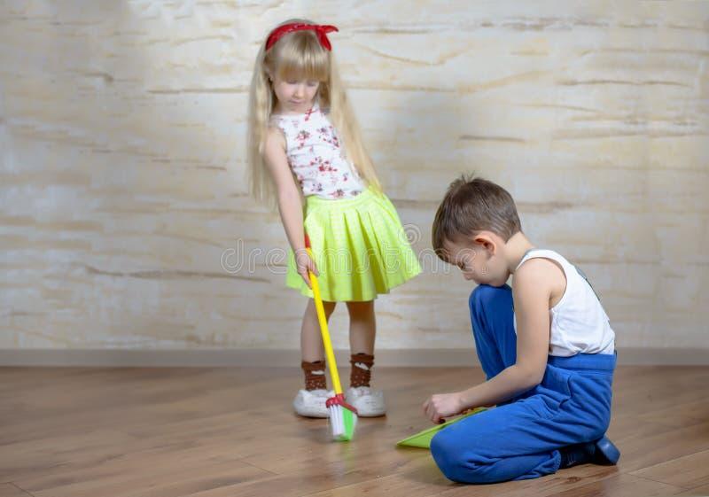 Śliczni dzieci używa zabawkarską miotłę i śmietniczkę fotografia stock