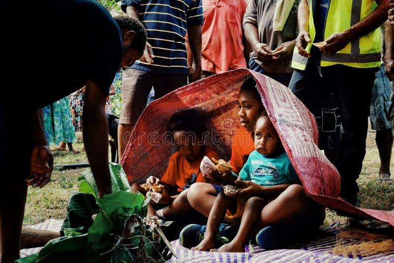 śliczni dzieciaki akceptuje ofiary lubią taro, ignam, tradycyjne wyplatać maty dla ich obrzezanie rytuału obraz stock