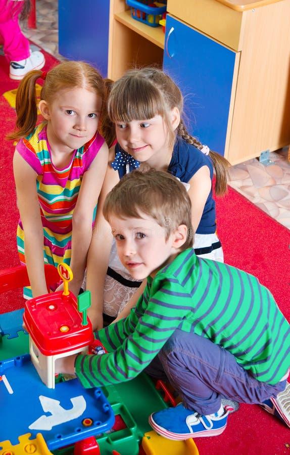 Śliczni dzieciaki bawić się przy dziecinem fotografia stock