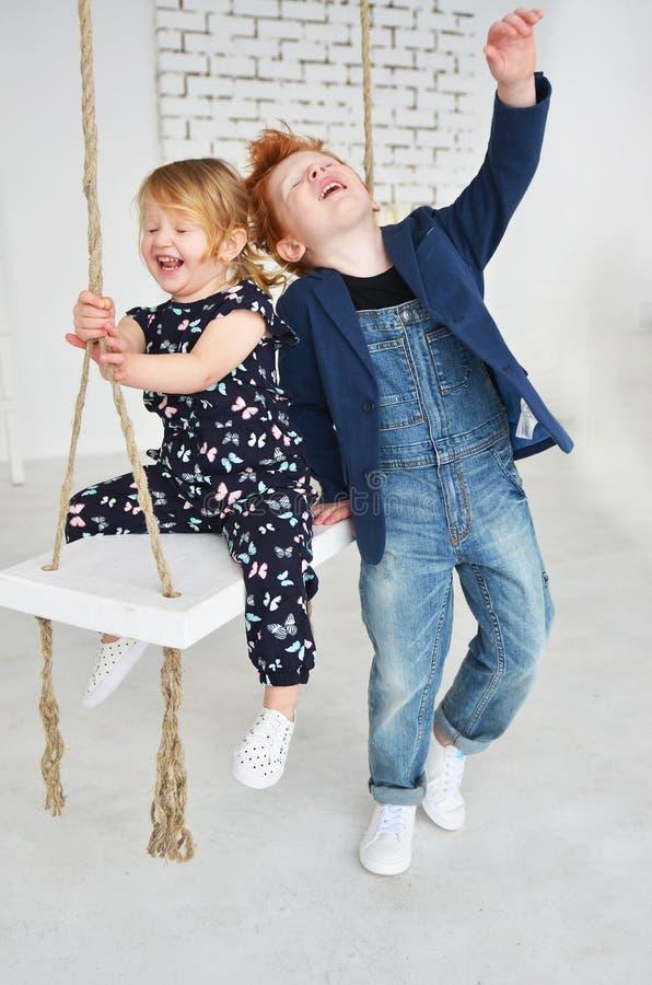 Śliczni dzieciaki brata i blondynki czerwona siostra zabawę na huśtawce obrazy royalty free