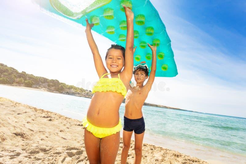 Śliczni dzieciaki z lotniczej materac koszt stały na plaży obraz stock