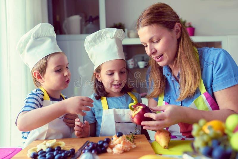 Śliczni dzieciaki z matką przygotowywa zdrową owocową przekąskę w kuchni obraz stock
