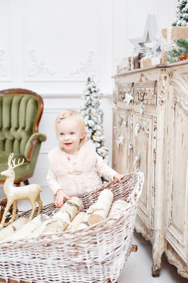 Śliczni dziecka i bożych narodzeń prezenty Małe dziecko ma zabawę blisko choinki w żywym pokoju Kochający rodzinni Wesoło boże na zdjęcie royalty free