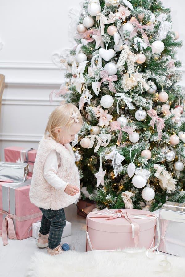 Śliczni dziecka i bożych narodzeń prezenty Małe dziecko ma zabawę blisko choinki w żywym pokoju Kochający rodzinni Wesoło boże na fotografia royalty free