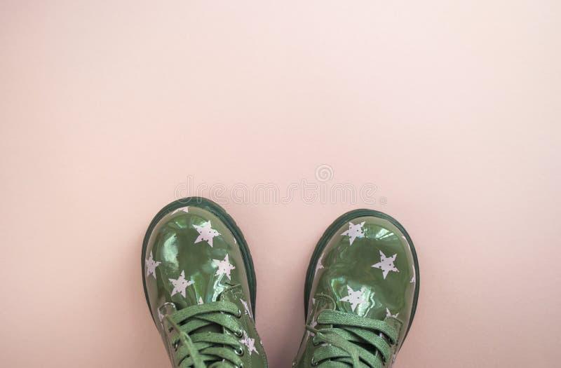 Śliczni dziecka ` s zielonego koloru buty na różowym tle fotografia stock