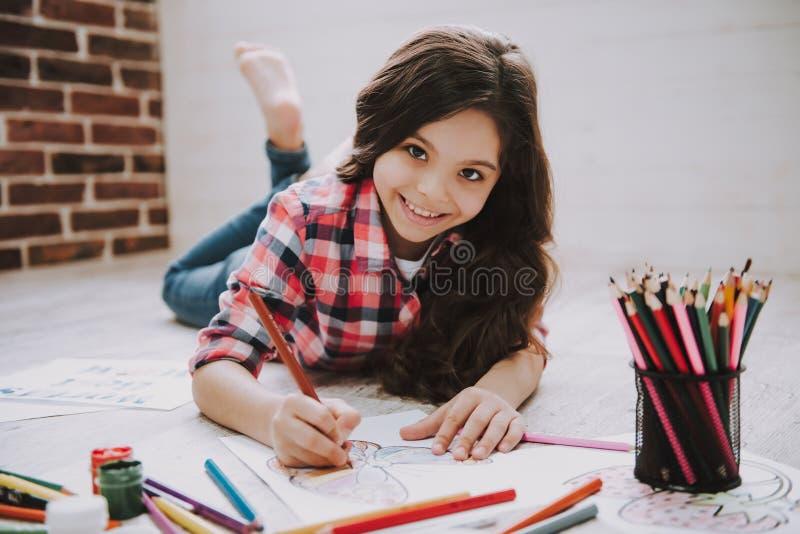 Śliczni dziewczyna rysunku obrazki z kolorów ołówkami zdjęcia stock