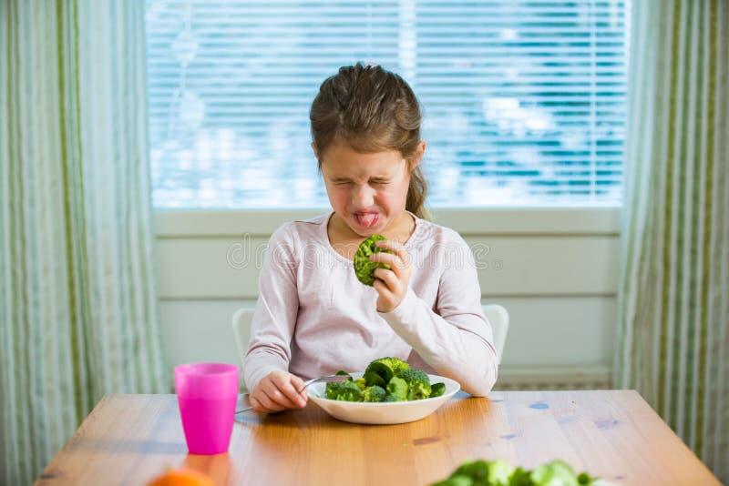 Śliczni dziewczyny łasowania szpinaki i brokuły przy stołem fotografia stock