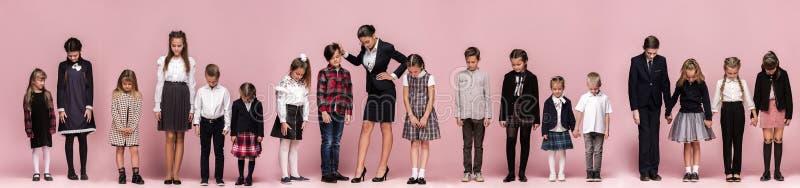 Śliczni eleganccy dzieci na różowym pracownianym tle Piękna nastoletnia chłopiec i zdjęcia stock
