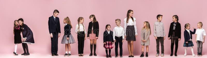 Śliczni eleganccy dzieci na różowym pracownianym tle Piękna nastoletnia chłopiec i obraz stock
