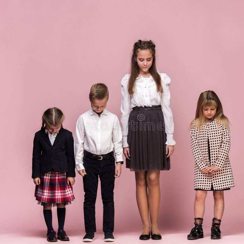 Śliczni eleganccy dzieci na różowym pracownianym tle Piękna nastoletnia chłopiec i obraz royalty free
