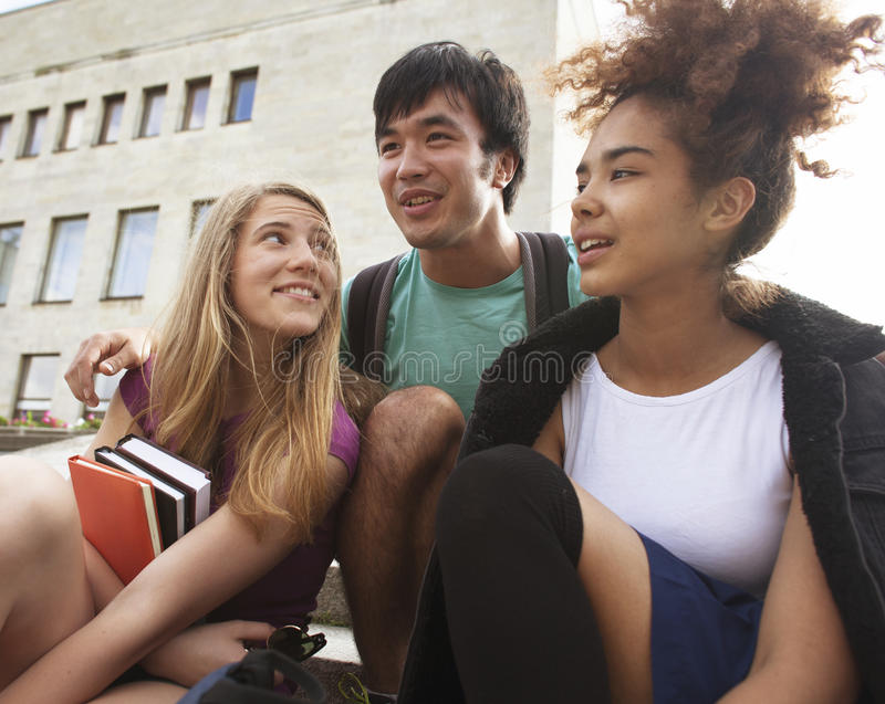 Śliczni grupowi teenages przy budynkiem uniwersytet obrazy stock