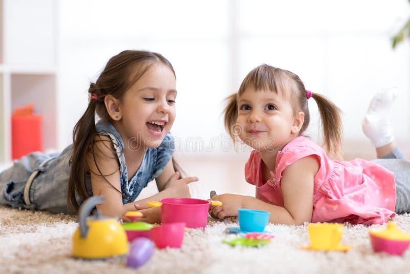 Śliczni małe dzieci bawić się z kitchenware podczas gdy kłamający na podłoga w domu fotografia stock