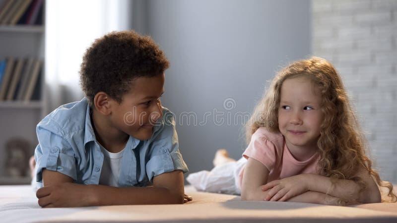 Śliczni małe dzieci clumsily flirtuje z each inny, pierwszy dzieciństwo miłość zdjęcie royalty free