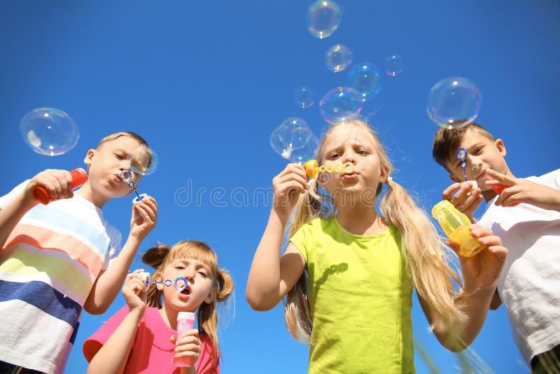 Śliczni małe dzieci dmucha mydlanych bąble na niebieskiego nieba tle zdjęcie stock