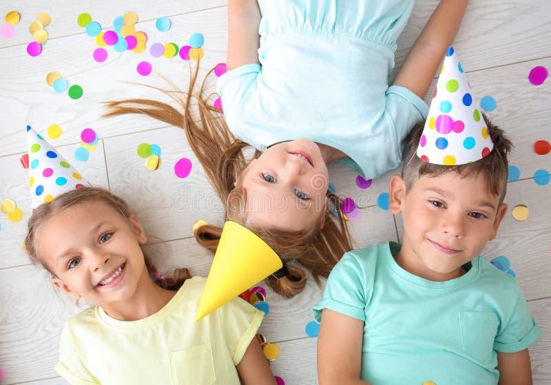 Śliczni małe dzieci kłama na podłodze podczas gdy świętujący urodziny w domu zdjęcie royalty free