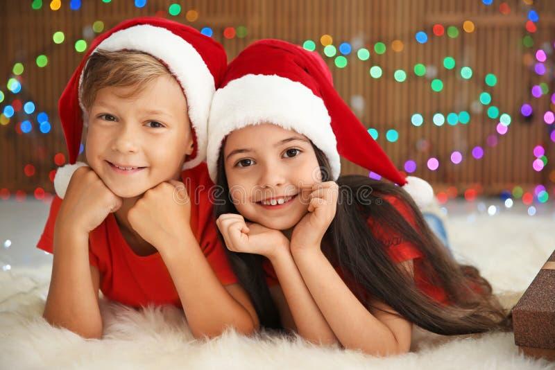 Śliczni małe dzieci kłama na podłoga w Santa kapeluszach zdjęcie stock