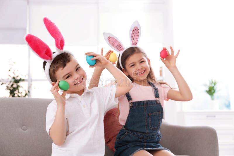 Śliczni małe dzieci w królików ucho kapitałkach bawić się z Wielkanocnymi jajkami fotografia stock