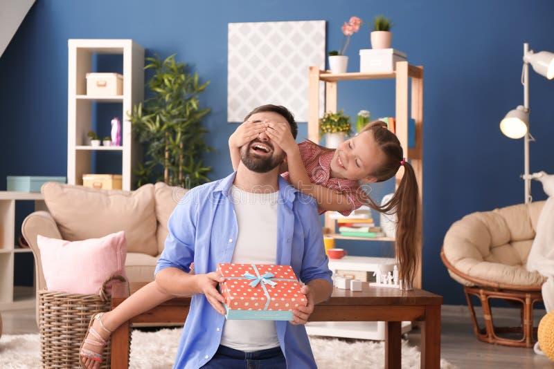 Śliczni małej dziewczynki nakrycia oczy jej ojciec podczas gdy dawać teraźniejszości indoors zdjęcie stock