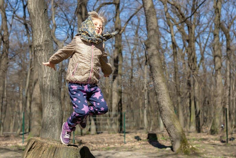 Śliczni mali blondyny żartują dziewczyny ma zabawę outdoors Dziecko w przypadkowej sport odzieży i chustki skokowej wysokości od  fotografia royalty free