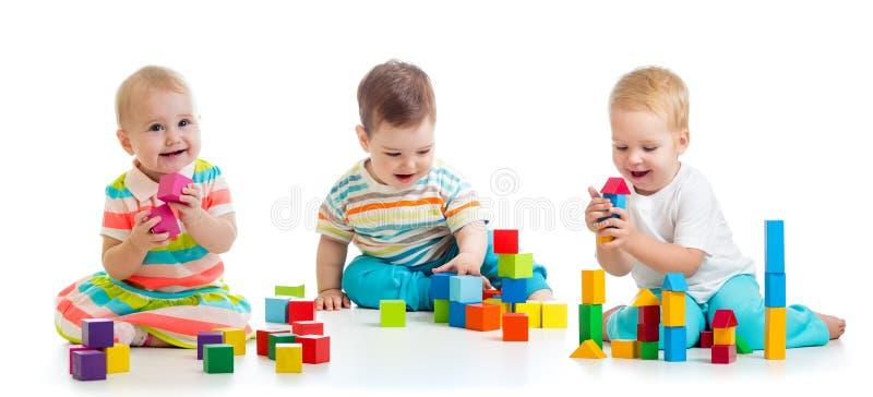 Śliczni mali dzieci bawić się z i ma zabawę zabawkami lub blokami podczas gdy siedzący na podłodze odizolowywającej nad białym tł zdjęcia stock