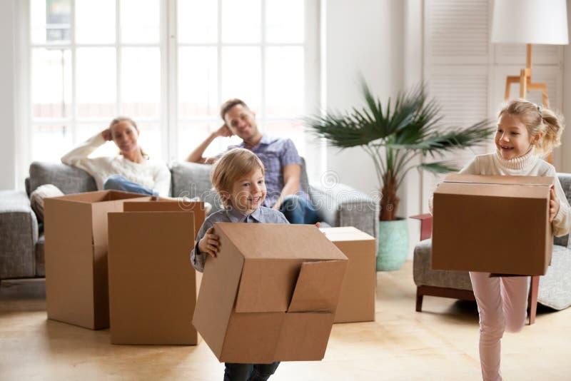 Śliczni mali dzieciaki niesie pudełka bawić się wpólnie na poruszającym dniu obrazy stock