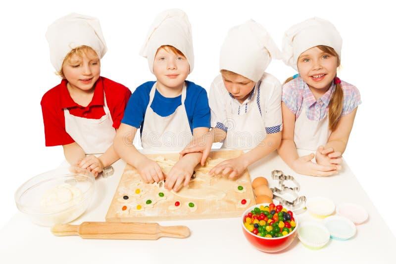Śliczni mali piekarzi przygotowywa cukierki wypełniających ciastka zdjęcia stock
