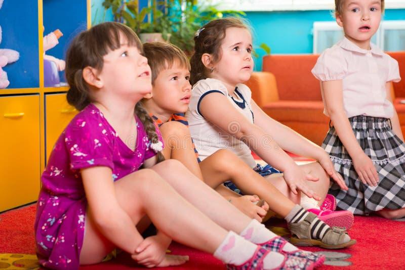 Śliczni preschoolers siedzi na podłoga i słuchaniu zdjęcia stock