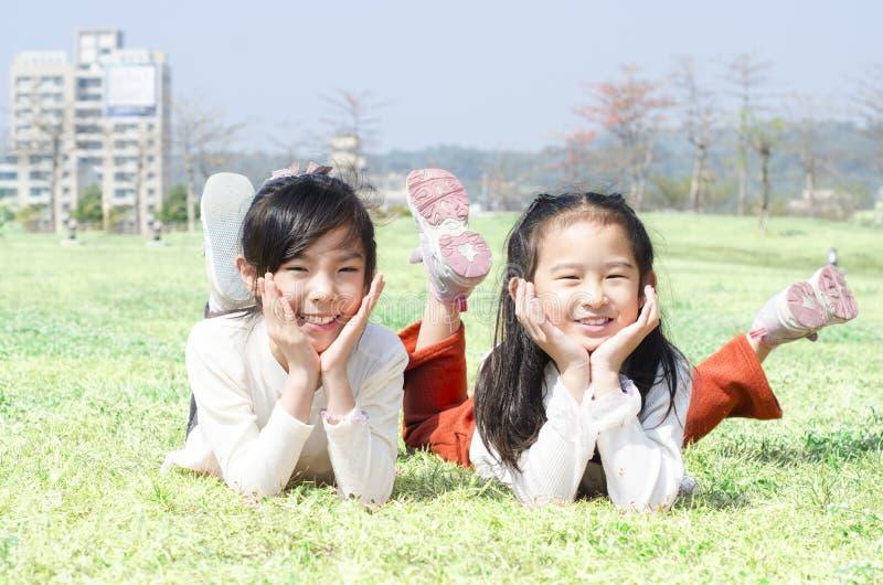 Śliczni szczęśliwi dzieci kłaść na trawie fotografia stock
