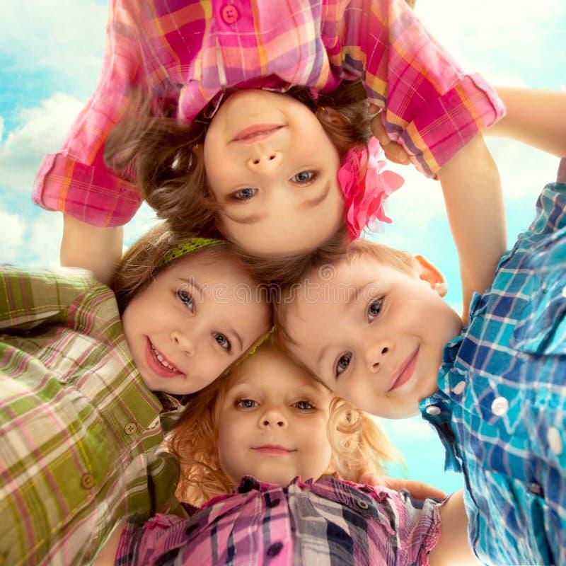 Śliczni szczęśliwi dzieciaki patrzeje w dół i trzyma ręki obrazy stock