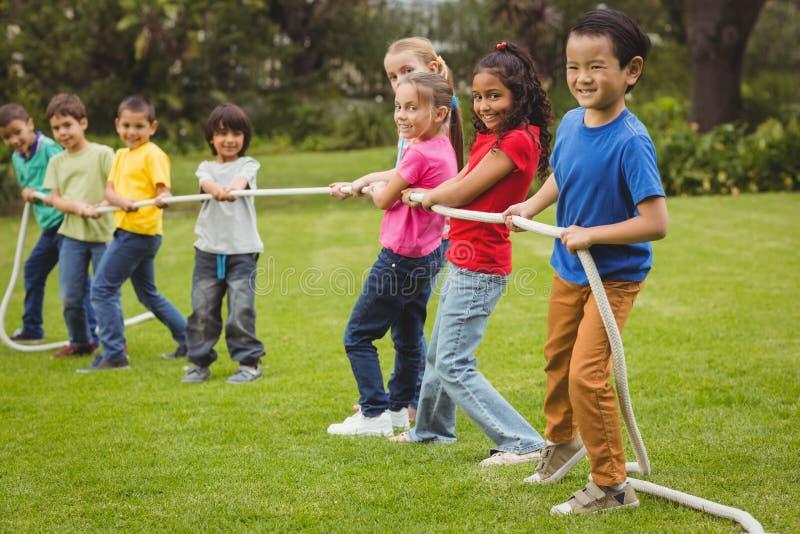 Śliczni ucznie bawić się zażartą rywalizację na trawie outside zdjęcia royalty free