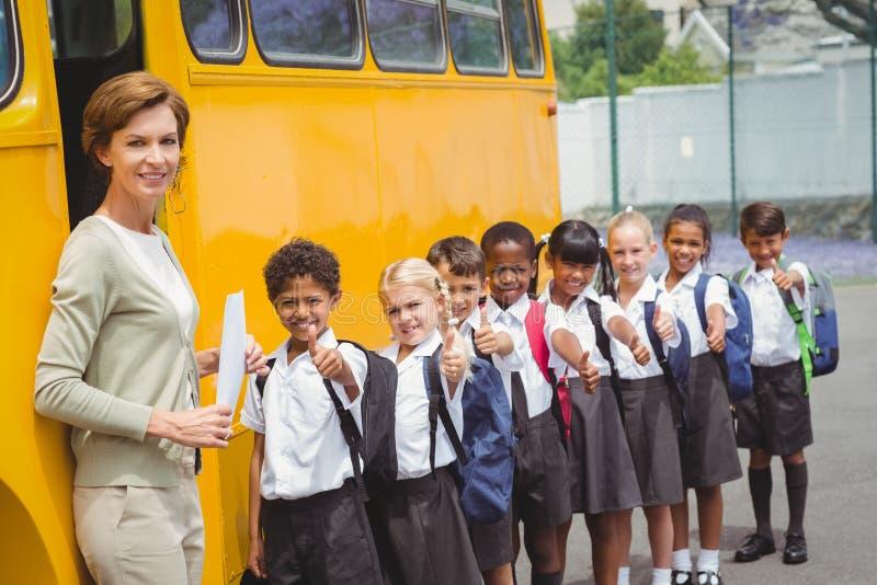 Śliczni ucznie czeka dostawać na autobusie szkolnym obraz royalty free