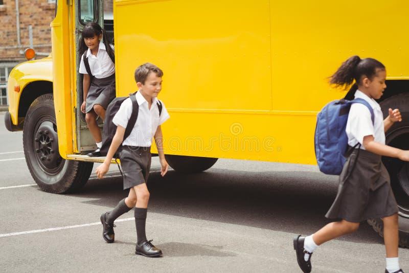 Śliczni ucznie dostaje daleko autobus szkolnego zdjęcia stock
