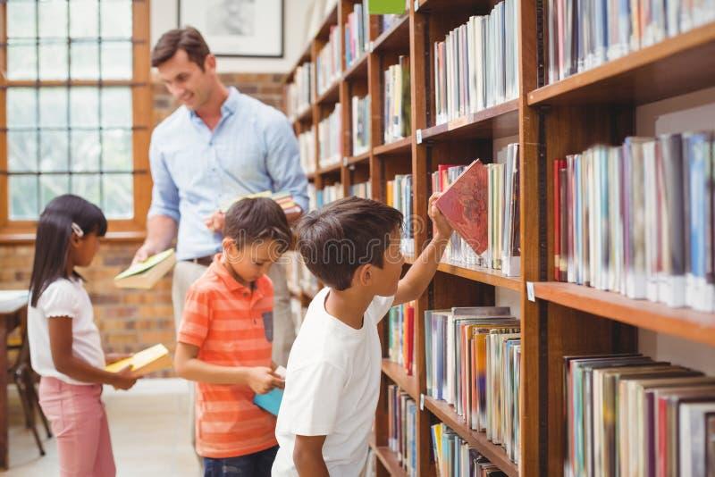 Śliczni ucznie i nauczyciel patrzeje dla książek w bibliotece zdjęcia stock