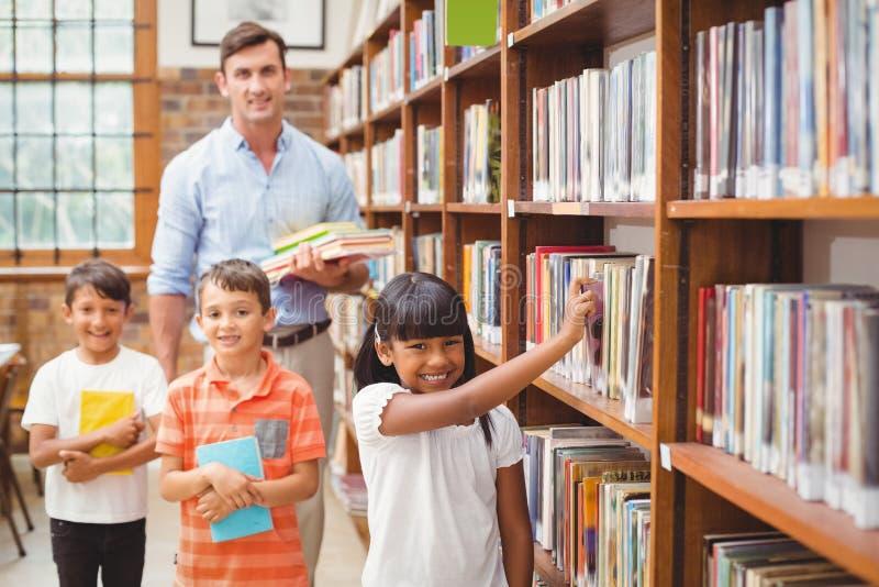 Śliczni ucznie i nauczyciel patrzeje dla książek w bibliotece obraz royalty free