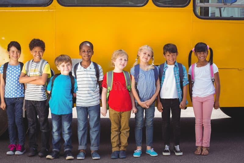 Śliczni ucznie ono uśmiecha się przy kamerą autobusem szkolnym obrazy royalty free