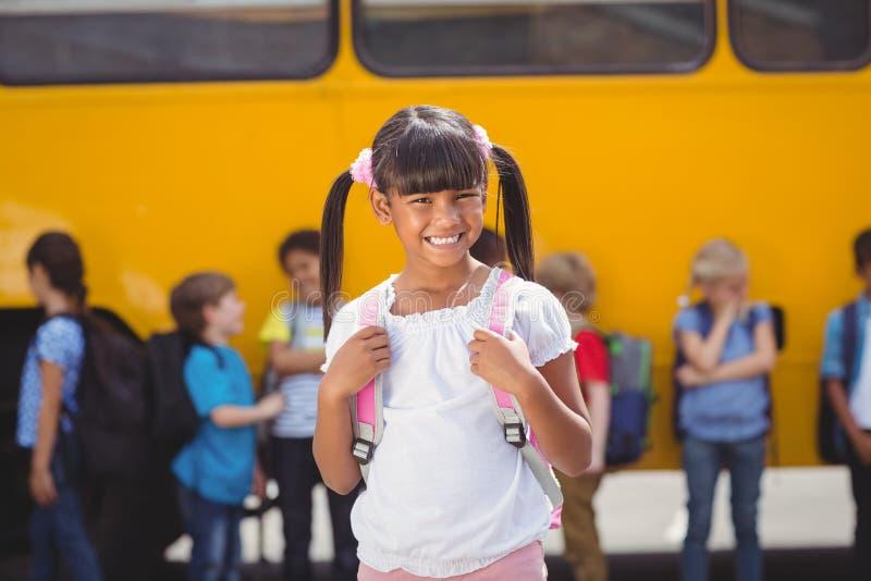 Śliczni ucznie ono uśmiecha się przy kamerą autobusem szkolnym zdjęcie stock