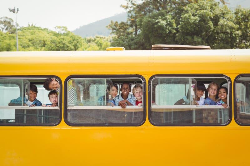 Śliczni ucznie ono uśmiecha się przy kamerą w autobusie szkolnym obrazy royalty free