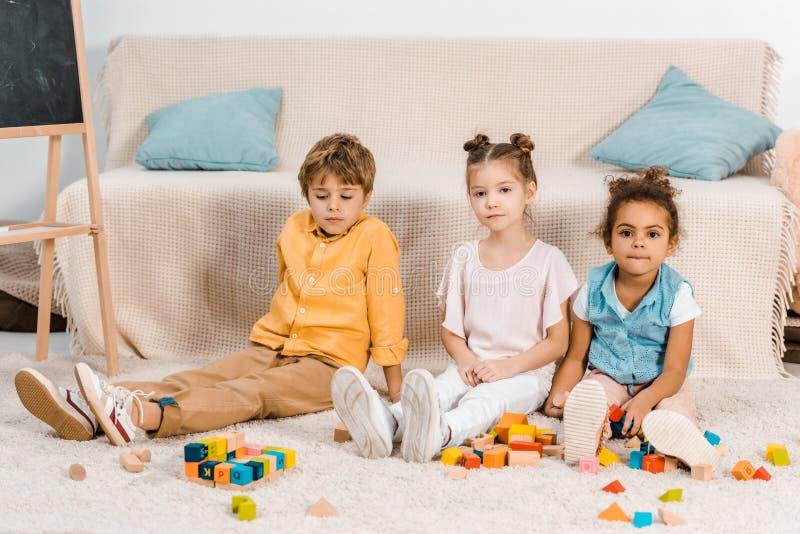 śliczni wieloetniczni dzieciaki bawić się z kolorowymi sześcianami i patrzeć fotografia stock