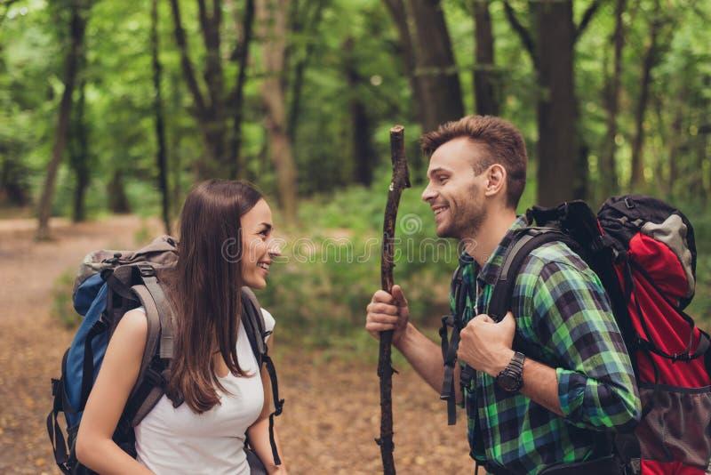 Śliczni z podnieceniem kochankowie wycieczkują w wiosna lesie, opowiadać i cieszyć się, jest ubranym wygodnych stroje dla wyciecz zdjęcia stock