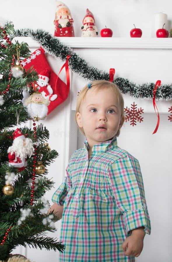 Śliczni zdziweni mała dziewczynka stojaki blisko choinki zdjęcie stock