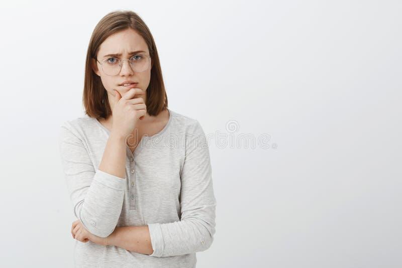 Śliczny żeński fajtłapy próbować rozwiązuje ciężkiego matematyki rzeszoto stoi rozważnego nadmiernego biel ściany nacierania podb fotografia royalty free