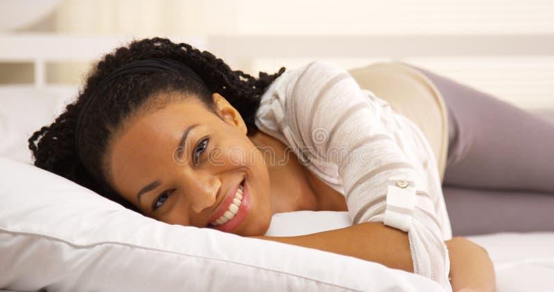 Śliczny afrykański kobiety lying on the beach na łóżkowej patrzeje kamerze obraz stock