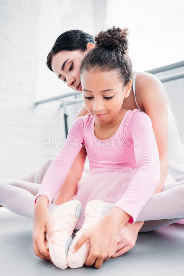 śliczny amerykanin afrykańskiego pochodzenia dziecko w różowym spódniczka baletnicy rozciąganiu podczas gdy trenujący z nauczycie zdjęcie stock