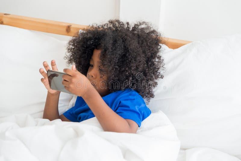 Śliczny amerykanina afrykańskiego pochodzenia dzieciak bawić się gry na pastylce zdjęcie stock