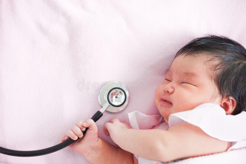 Śliczny azjatykci nowonarodzony dziewczynki dosypianie i mienie stetoskop fotografia stock