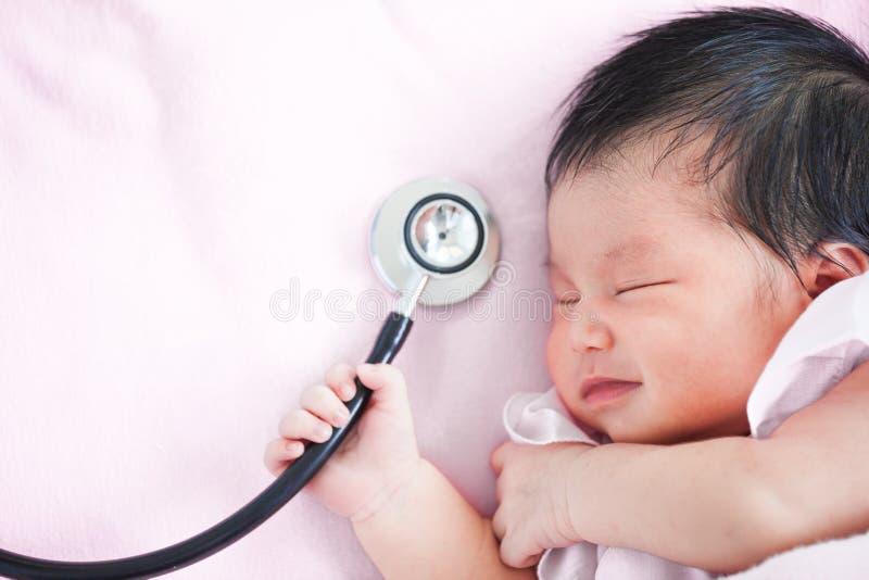 Śliczny azjatykci nowonarodzony dziewczynki dosypianie, stetoskop i obraz royalty free