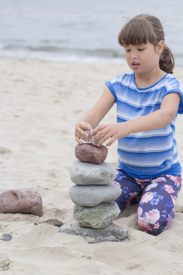 Śliczny berbeć na plaży bawić się z kamieniami fotografia stock