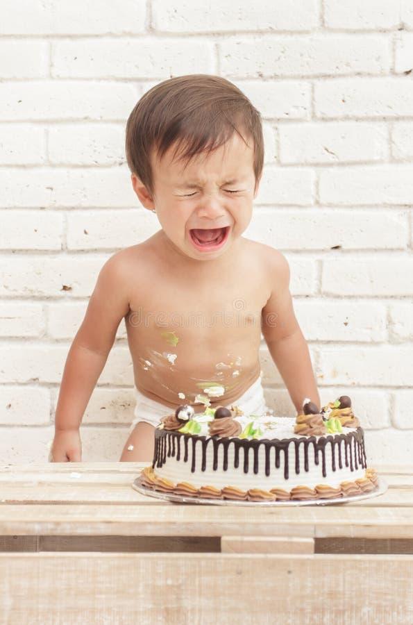 Śliczny berbecia płacz podczas gdy bawić się roztrzaskanie tort zdjęcia royalty free
