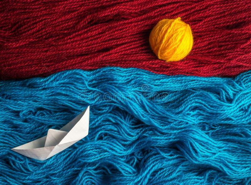 Śliczny biel origami łódkowaty unosić się na fala woolen nić w kierunku zmierzchu zdjęcie royalty free
